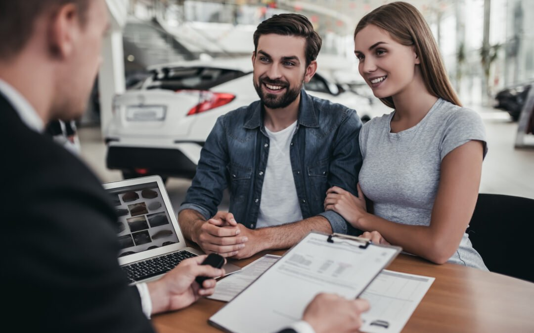 Happy beautiful couple is buying a new car at dealership.